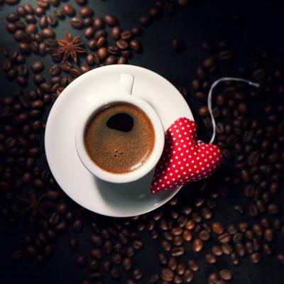 Coffee espresso with coffee beans on a background and red plush heart, top view. Valentine's day or love concept